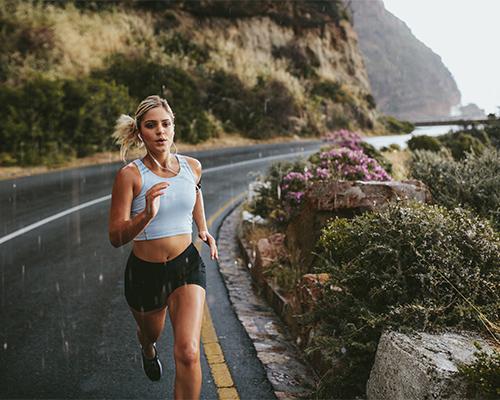 Fitness woman running on highway