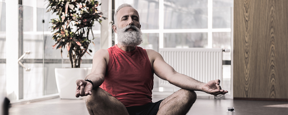 Pleasant old man is enjoying yoga in fitness center